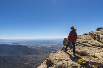boy with long hair standing at the edge of a mountain peak looking down at the world below