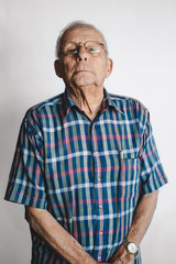 Serious older man on white studio background