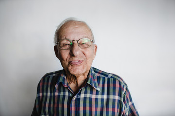 Playful senior man removing dentures and laughing