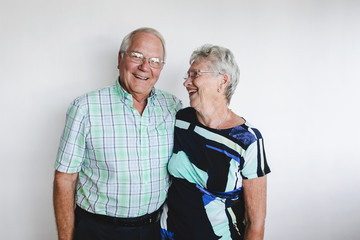 Happy senior couple looking at camera on white background