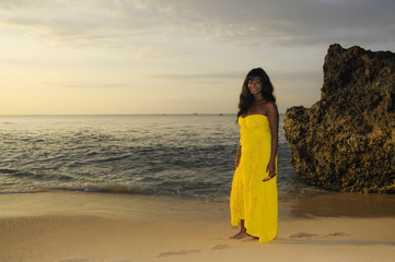 glamorous African American black woman in chic and elegant summer dress posing relaxed walking on summer sunset beach