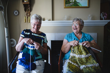 Two senior women knitting together nd laughing
