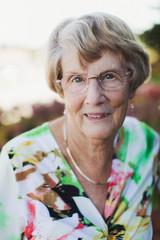 Happy portrait of elderly woman outside near flowers