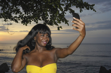 glamorous African American black woman in chic summer dress taking selfie picture or video on mobile phone
