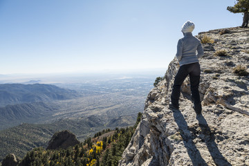 Woman standing at the edge of a cliff overlooking mountains and a city below