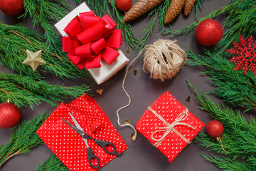 Gift wrapping for Christmas on a dark background spruce branches, cones, snowflakes, the concept of a holiday and the New Year's atmosphere
