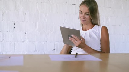 Wall Mural - Businesswoman with tablet in her office, working.