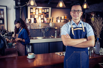 Portrait of asian barista with arms crossed at counter in coffee shop. Cafe restaurant service, Small business owner, food and drink industry concept.
