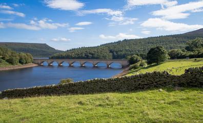widok na jezioro z mostem murem z kamieni w słoneczny dzień