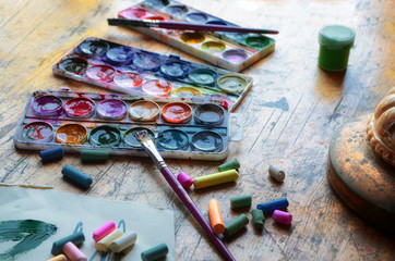 Old pastels crayons, three palettes of different colors, colorful paint tubes and artistic brush on vintage wooden background. Used tools for drawing and painting art.  Visual arts concept.