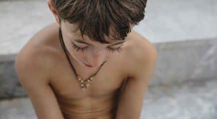 Closeup of a boy looking down, captured from above