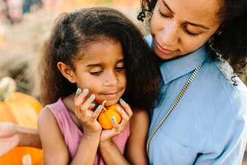 A mother holding her young daughter at a pumpkin patch