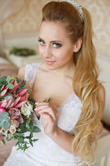 Beautiful young Bride with blonde hairs in a bedroom. Classic white wedding dress. Full-length portrait
