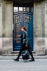 Woman walking on the street and using her smartphone