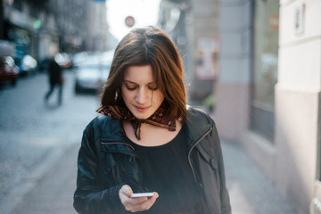 Young beautiful woman using a mobile phone on the street