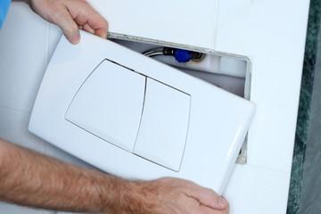 Sanitärmonteur installiert Spülkasten