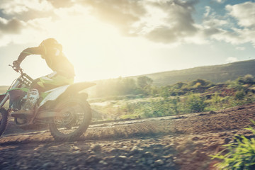 Motocross MX pilot in a turn during sunset on a dirt track