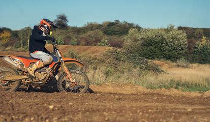 Motocross enduro rider accelerating in dirt track