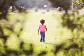 Portrait of a young girl walking away into an open field