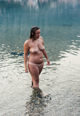 Young naked woman getting out of the water