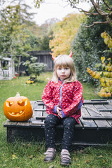 Little girl with red horns in garden at Halloween