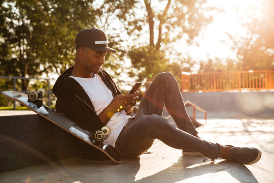 Young african man with a skateboard using smartphone
