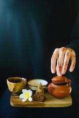 Teapot in tattooed hands