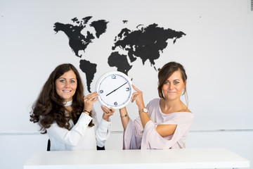 Two young girls twins with clock on the background of the world map