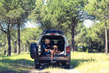 Man with dog sitting in off road car boot