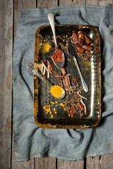 Several species on metal tray on a vintage piece of fabric with a  worn wood surface