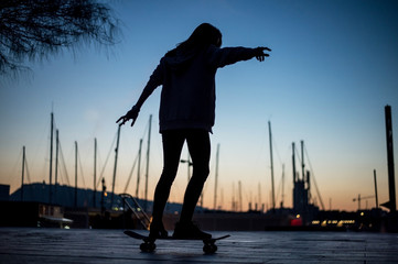Young woman skating in the port of Barcelona at sunset