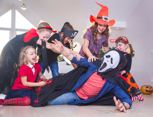 Dad in monster costume scares children at Halloween party