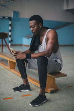 Young man checking his phone during workout