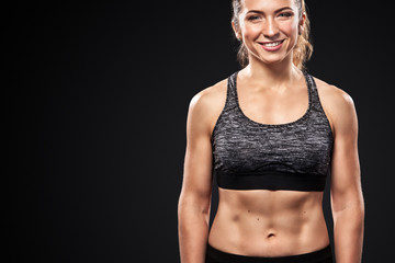 Sporty beautiful woman doing fitness exercising at black background to stay fit.
