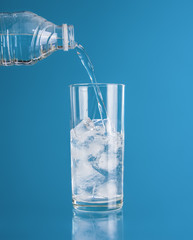 Glasses of water with ice cube on blue background