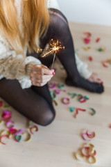 From above - woman holding a sparkler at home with confetti on the floor