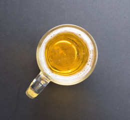 Top view of a glass of beer on dark background