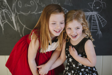 Two young girls dressed up in their holiday best hold hands laughing.
