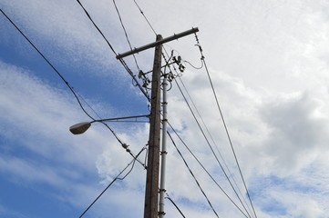Wires and cables routed through the town on a telephone pole with a street light