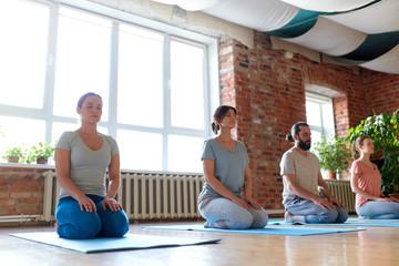 group of people meditating at yoga studio