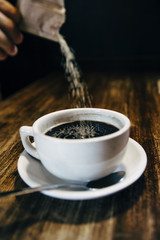 Pouring sugar into a cup of black coffee