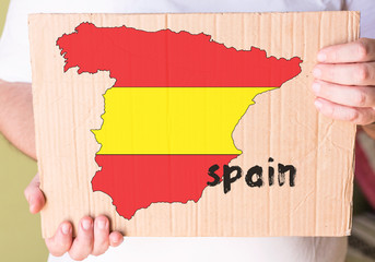 spanish map on cardboard in hands man