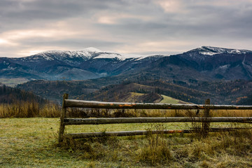 fence on grassy meadow in autumn. landscape of mountain ridge with snowy tops in the distance. gorgeous and unusual countryside scenery
