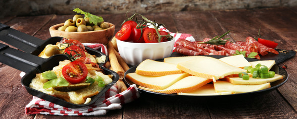 Delicious traditional Swiss melted raclette cheese on diced boiled or baked potato served in individual skillets with salami..