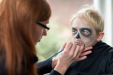 Mother Applying Little Boys Halloween Costume Make Up