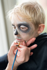 Mother Applying Halloween Costume Make Up for Blonde Boy