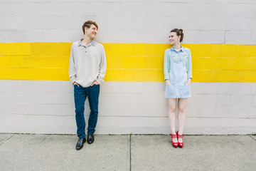 Urban young couple standing against a wall