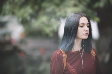 young woman with blue hair walking on the street
