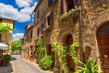 Beautiful narrow street with sunlight and flowers in the small magical and old village of Pienza,...