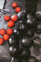 Red and black weighted balls in a gym.